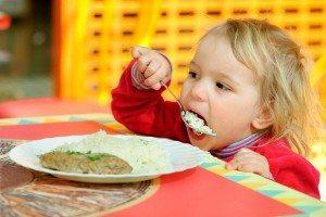 дівчинка їсть кашу